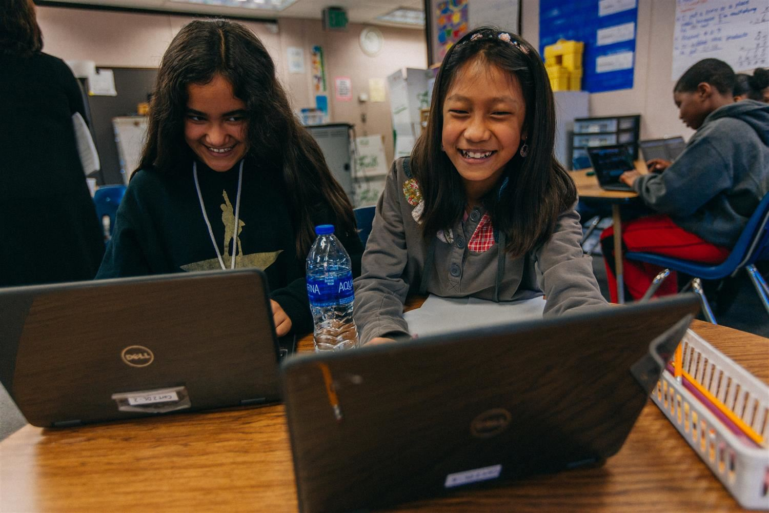 Two students laughing on computer