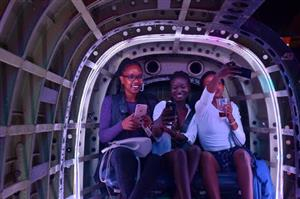 Three girls inside a space simulator